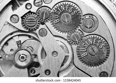 Background with the inscription BUSINESS. Black white background with metal cogwheels clockwork. Macro. Conceptual photo for your successful business design. Concept teamwork