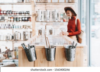 Background of interior in zero waste shop. Customer buying dry goods and bulk products in plastic free grocery store. Image of conscious shopping, sustainable small businesses, minimalist lifestyle