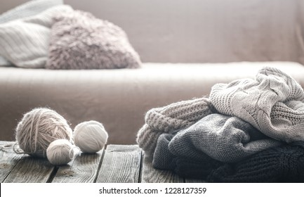 Background with knitted sweaters on a wooden background, the concept of warm clothes