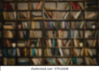 The background is a large bookshelf or book case on the wall. Many books in the side. Blurred background. The place to insert the text.