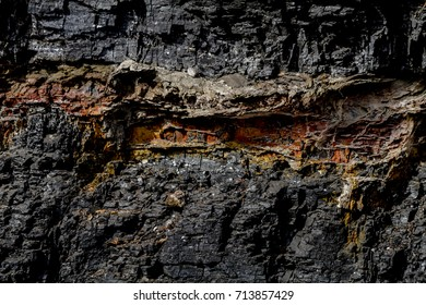 Background of layers of black coal and petrified wood in rock canyon wall