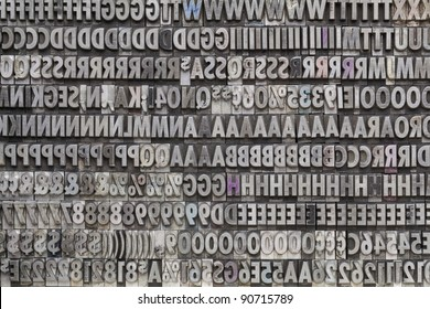background of letters, numbers and punctuation symbols in old grunge metal movable typeset