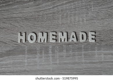 """Background. Letters on wooden table. """"Homemade""""."""