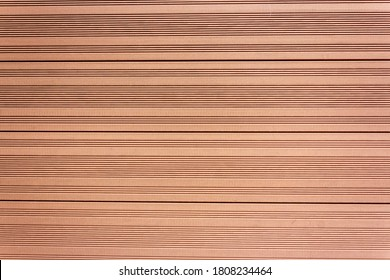 Background of light brown boards with grooves made of vertical tongue and groove boards.
