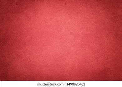 Background of light red suede fabric closeup. Velvet matt texture of wine nubuck textile with vignette.