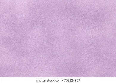 Background of light violet suede fabric closeup. Velvet matt texture of lilac nubuck textile.