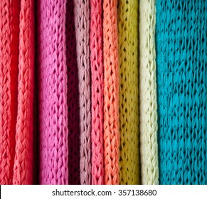 Background of lines of bright and colorful knit fabric in pink, lilac, peach, yellow, green and teal blue