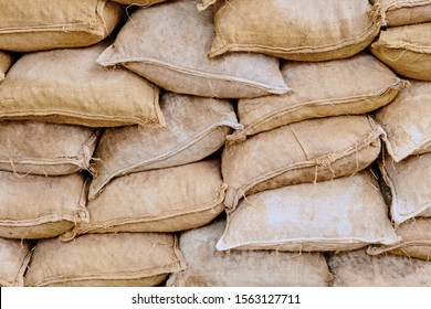 Background of lying dirty sandbags. Sandbag flood protection wall texture, texture. Bags to strengthen the defensive structure during the battle.