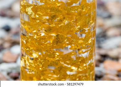 Background - macro view of real gold flakes in a bottle