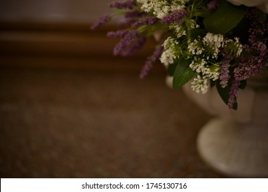 The background is made of a fragment half of artificial small white and purple flowers in a vase on the leg, right. A blurred dark frame image.