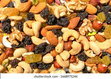 Background made of mixed nuts and raisins. Healthy snack and food. Cashew, almond, raisins, walnut, pistachio. Top view. Assorted nuts and dry grapes.