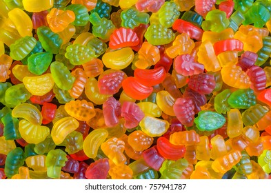 background of many bright and colored jelly sweets with free space for text, top view