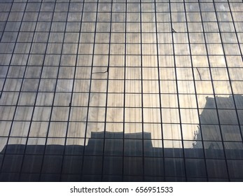 Background of many glass window of outdoor building in the city is the modern design architecture in low angle view