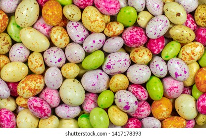 background of many multicolored candies or chocolates in glaze