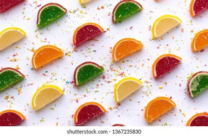Background of marmalade slices with colored coconut flakes. Fruit marmalade with orange, lemon, grapefruit and kiwi flavors.