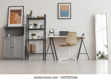 Background of minimal home office desk in modern apartment decorated by plants and abstract art, copy space