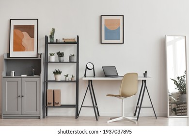 Background of minimal home office workplace in modern apartment decorated by plants and abstract art, copy space