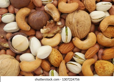 Background of mixed nuts, walnuts, cashews, almonds, macadamia nuts, pistachios, peanuts