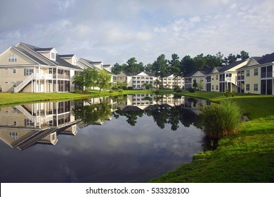 Background with a modern neighborhood with buildings around the pond. Houses and trees reflected in the tranquil water during beautiful cloudy morning.