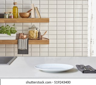 Background modern tiles wall, white table with modern kitchen accessories, interior design