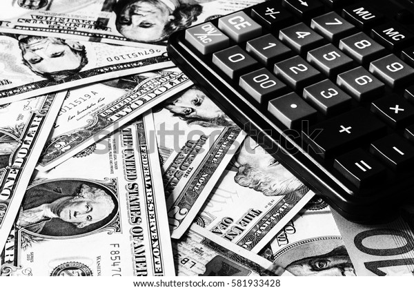 Background with money american dollar bills and black calculator. Cash money. Black and white image.