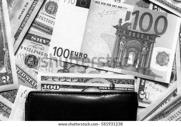 Background with money american dollar and euro bills and leather wallet. Cash dollars and euros. Black and white image.