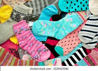 Background from multi-colored socks. Socks for the cold seasons. Clothing from knitwear for autumn and winter. Blue, red, green, yellow socks of different sizes.