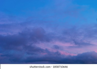 Background of mystery purple and pink clouds on blue sky at evening after sunset. Telephoto zoom photo shot