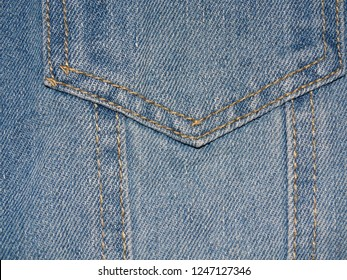 Background of natural blue and white jeans, firmware pockets for jackets. Tailoring, casual wear, comfortable and practical clothing.