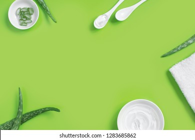 Background with natural cosmetics of aloe vera juice, fresh leaves of aloe on green, copy space