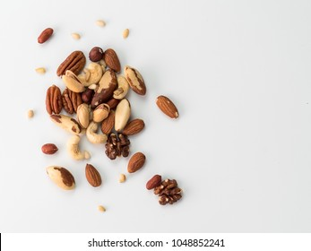 Background of nuts - pecan, macadamia, brazil nut, walnut, almonds, hazelnuts, pistachios, cashews, peanuts, pine nuts - with copy space. Isolated one edge. Top view or flat lay