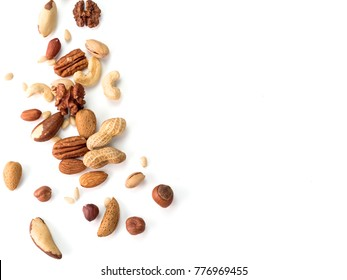 Background of nuts - pecan, macadamia, walnut, almonds, hazelnuts, and other - with copy space. Isolated one edge. Top view or flat lay