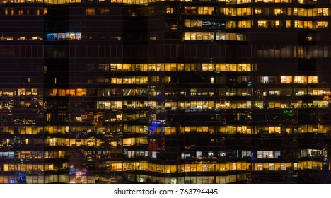 Background of Office Building Glow At night with People working Late as Modern City Working Lifestyle Concept.