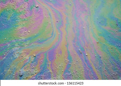 Background of an oil slick on the asphalt.