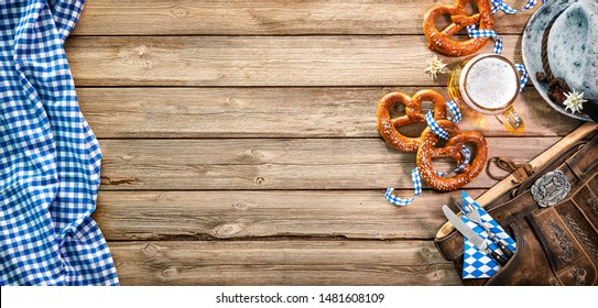 Background for Oktoberfest with Bavarian Lederhosen, hat, edelweiss, silverware, pretzels and beer stein on wooden tableHallo