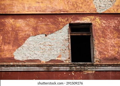 Background of old adobe peeled brick wall with a window.