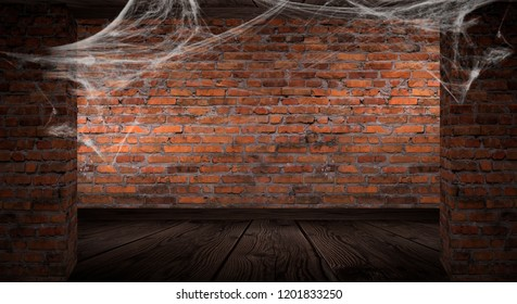 The background of the old brick wall, cracks in the wall, cobweb, neon light. Old basement room with cobwebs, smoke, smog. Dark gloomy background for the holiday of Halloween.