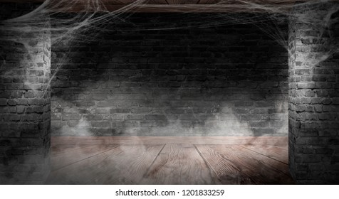 The background of the old brick wall, cracks in the wall, cobweb, neon light. Old basement room with cobwebs, smoke, smog.Dark halloween background. Glowing pumpkin on a concrete floor with fog, smog,