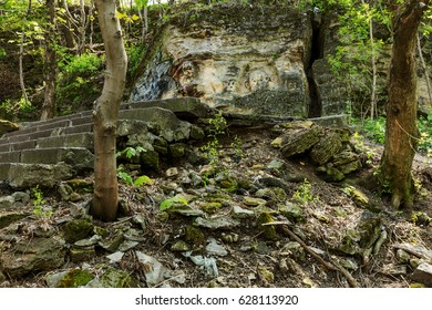 Background of old destroyed stone steps of staircase in magical surroundings of stone mountains and fresh greenery. Very old stone flask in cracks and traces of landslide after earthquake