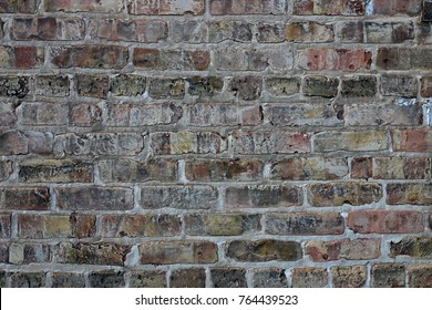 A background of an old, grungy, urban brick and mortar exterior wall made of tan and grey stone.