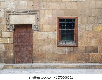 Background of old stone bricks wall with grunge wooden closed door and window with iron grid, Cairo, Egypt