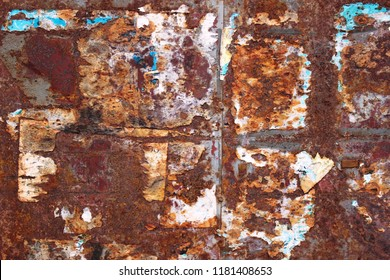 Background of old torn and peeling advertising flyers on a rusted metal wall.