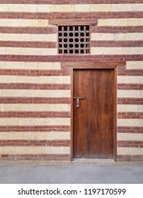 Background of old wall with red bricks and yellow stones, wooden closed door and window, Cairo, Egypt