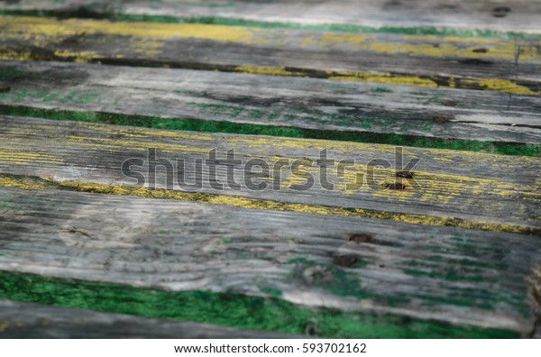 Background of old wood with traces of old paint and green with moisture iest with a number of nails driven into