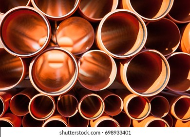 Background of orange plastic pipes used at the building site. Texture and pattern of plastic drainage pipe. Light through tubes.