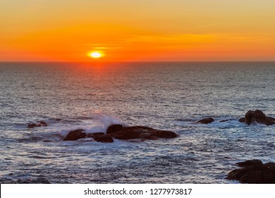 Background of orange sunset over the oceanic horizon with waves beating on the rocks at foreground
