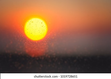 Background overlay of a defocused sun during sunset seen through the window after light rain