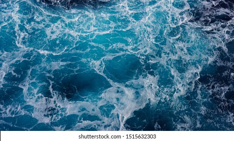 background pacific ocean during a typhoon, bright blue color of a sea splashing wave, texture of sea foam. abstraction of ripped water waves in the ocean in a storm sunlight. turbulent ocean