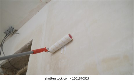 Background of paint roller standing against blank white wall. Lubricates the wall with a primer. A worker fills the wall with a white primer. Paint roller and primer.