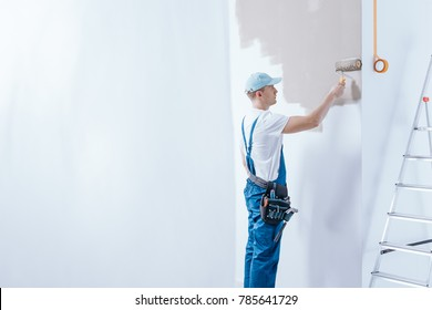 In the background painter in blue overalls painting white wall using roller